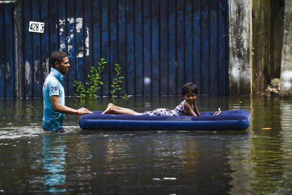 Un hombre transporta a un niño por una calle inundada en Colombo, Sri Lanka. - Sputnik Mundo