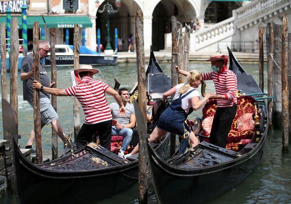 Los gondoleros venecianos ayudan a los turistas a subir a las góndolas. - Sputnik Mundo
