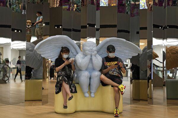 Dos visitantes observan sus teléfonos mientras permanecen junto a la escultura de un ángel en un centro comercial de Pekín, China. - Sputnik Mundo