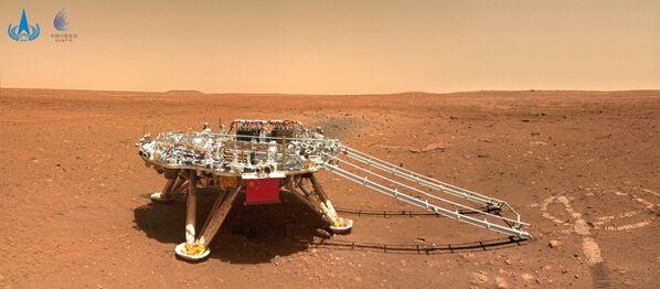Zhurong, parte de la misión china Tianwen-1, ha tomado numerosas fotos de Marte desde su llegada al planeta rojo el pasado 15 de mayo. Entre ellas, se pueden apreciar su lugar de aterrizaje, el paisaje marciano e incluso un selfi del rover con la plataforma de aterrizaje.En la foto: el módulo de aterrizaje Tianwen-1 en la superficie de Marte, fotografiado por el rover Zhurong. - Sputnik Mundo