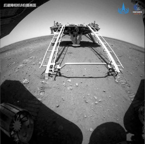 En esta foto, el rover Zhurong desciende desde el módulo de aterrizaje hasta la superficie de Marte. - Sputnik Mundo
