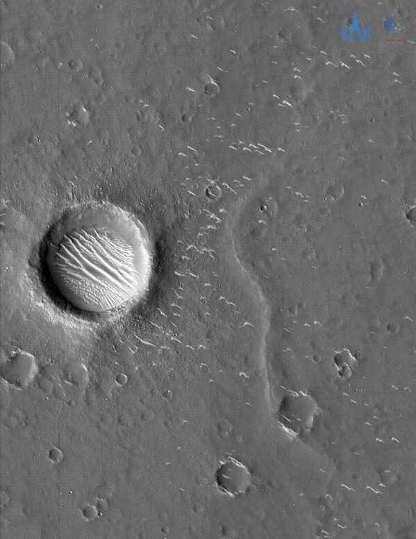 Además, la sonda tomó dos fotografías en blanco y negro de alta resolución a una distancia de entre 330 y 350 kilómetros de la superficie de Marte. En ella es posible ver pequeños cráteres, crestas y dunas. El diámetro del cráter más grande (en la foto) se estima en unos 620 metros. - Sputnik Mundo