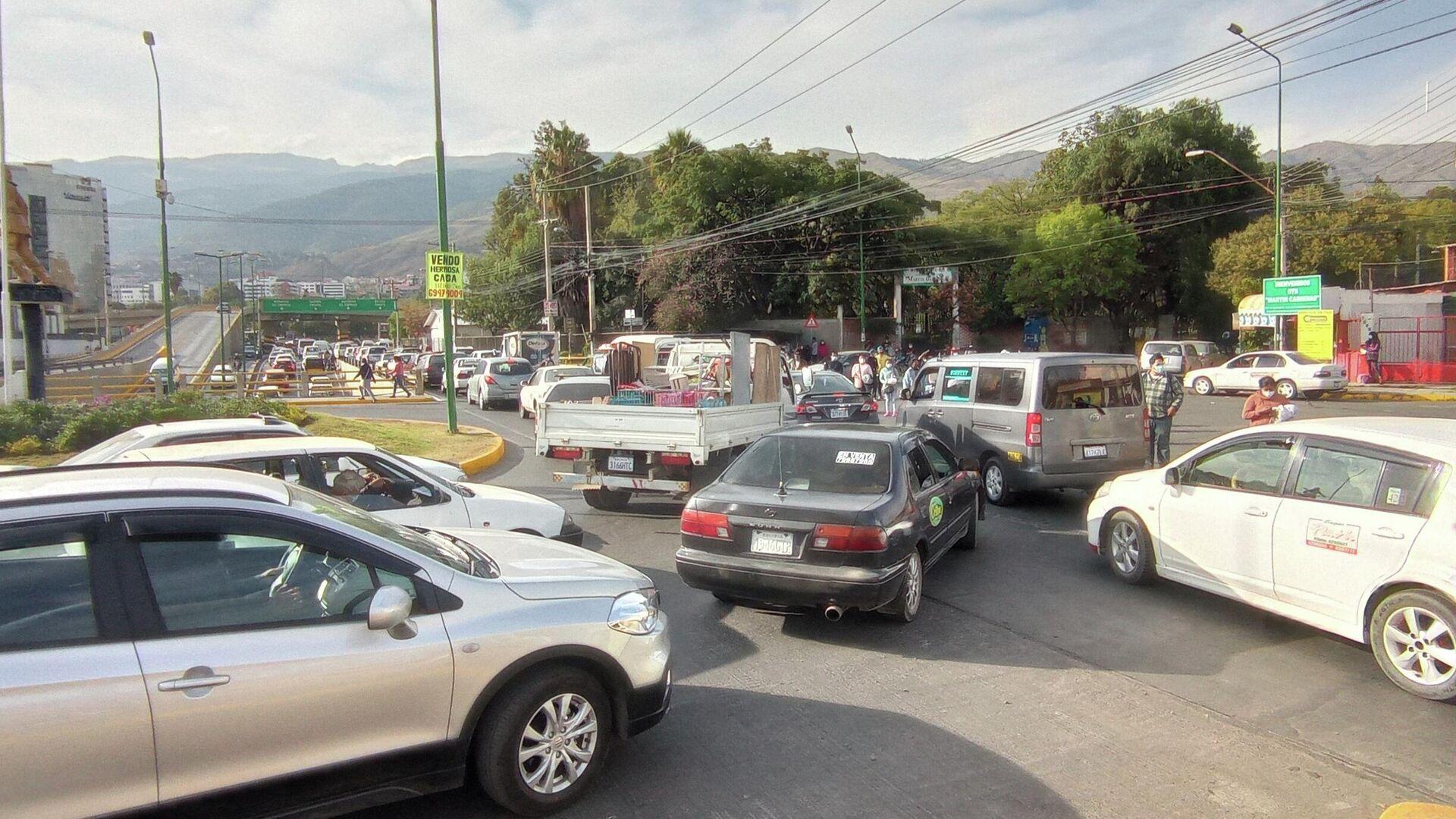 Viernes 11 de junio, 15:57. Faltan tres minutos para el inicio del encapsulamiento, que se extenderá hasta el amanecer del lunes 14. En el distribuidor Muyurina se aglomeran los autos que abandonan la ciudad de Cochabamba y se dirigen al municipio lindero de Sacaba. - Sputnik Mundo, 1920, 14.08.2021