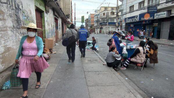 17:04. Resignadas por la ausencia de clientes, las señoras que tienen sus puestos en el mercado de La Cancha (el más grande de Cochabamba) cerraron sus comercios y se reunieron en torno a la casera que les vende comida, a manera de despedir la semana. - Sputnik Mundo