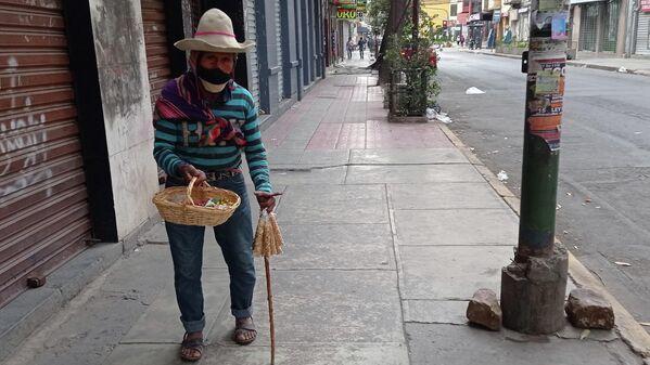 17:14. Tata Eulogio camina frágilmente apoyado en su bastón por la calle San Martín. Vende maní tostado y caramelos. Aunque ya se esfumó su clientela, no pierde la esperanza de recaudar una moneda más antes de que anochezca. - Sputnik Mundo