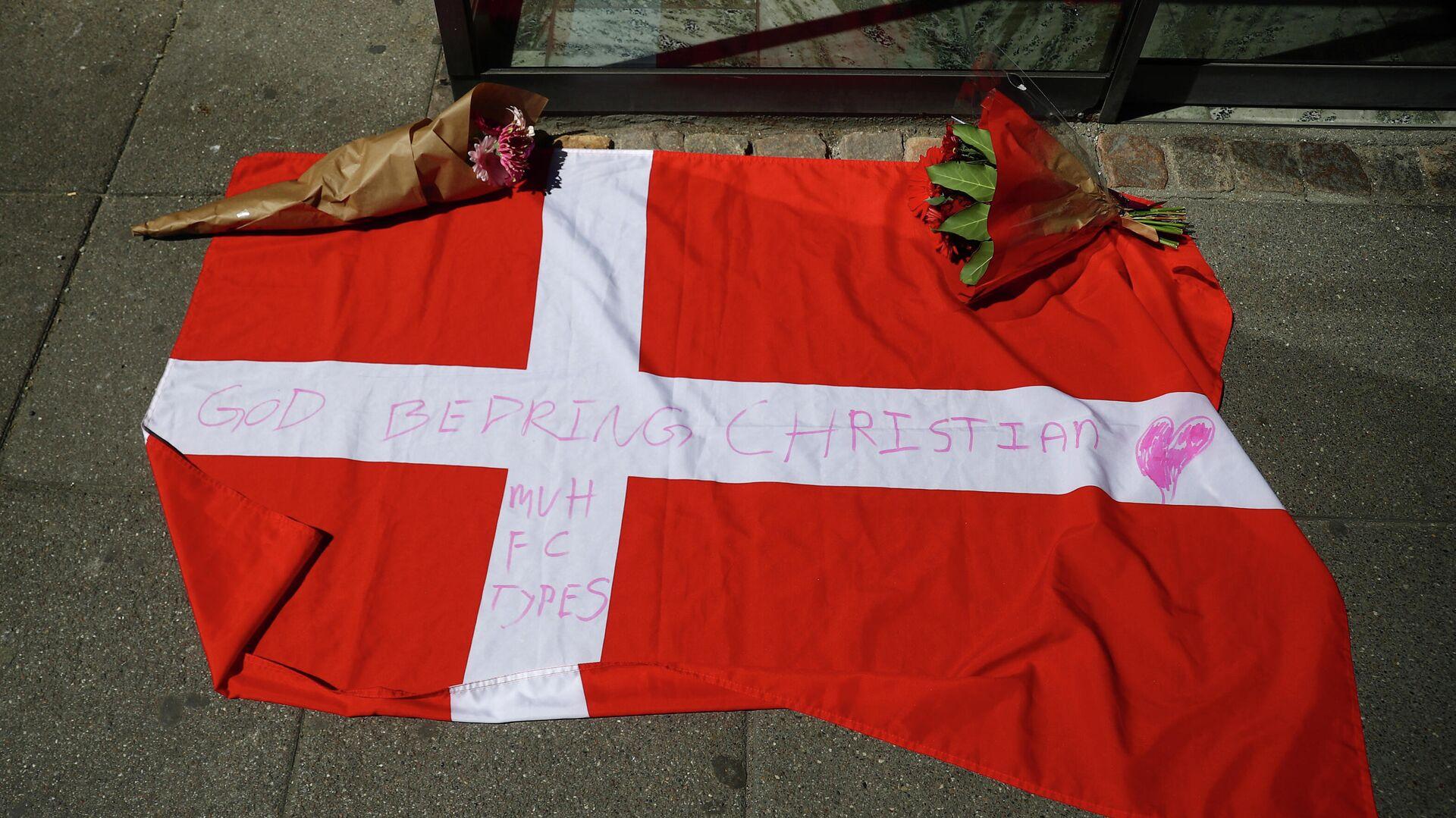 Bandera de Dinamarca y flores frente al hospital donde se encuntra el futbolista Christian Eriksen - Sputnik Mundo, 1920, 13.06.2021