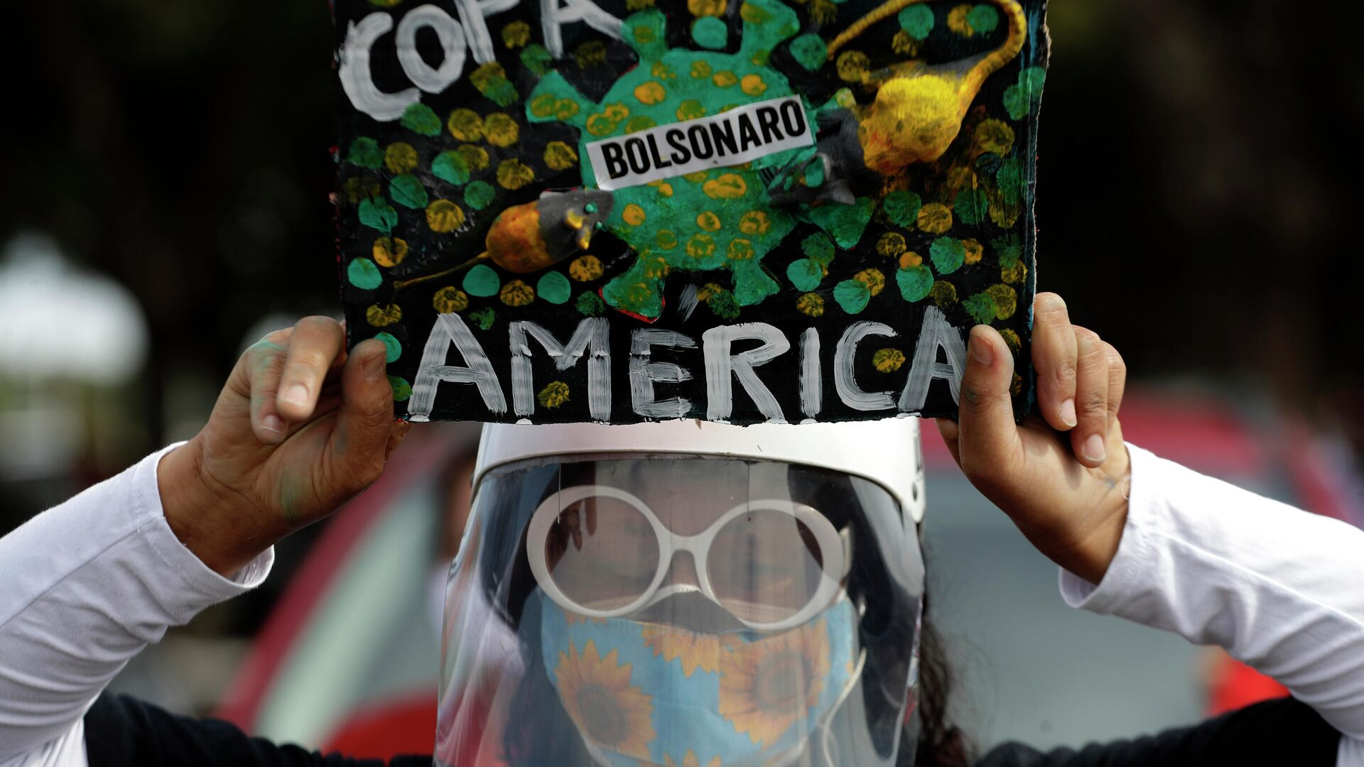 Una mujer con mascarilla protesta contra la realización de la Copa América en Brasil en plena pandemia de COVID-19 - Sputnik Mundo, 1920, 14.06.2021