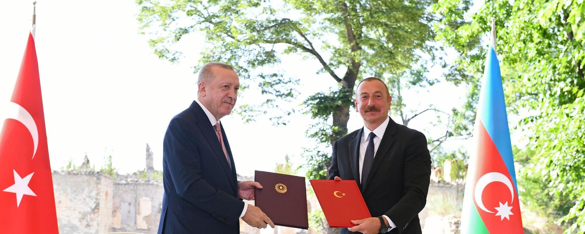 Recep Tayyip Erdogan, el presidente de Turquía (izda.), con su homólogo azerí Ilham Aliyev (dcha.) firmando una declaración de relaciones aliadas  - Sputnik Mundo, 1920, 15.06.2021