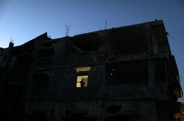 El  fondo de viviendas y la infraestructura fueron muy dañados, ya que los ataques aéreos se lanzaron contra los edificios residenciales, las escuelas, las mezquitas, las carreteras, las instituciones gubernamentales, la canalización, las tuberías de agua, los  hospitales, los centros de urgencias, etc.En la foto: un niño palestino en una ventana de un edificio destruido. - Sputnik Mundo
