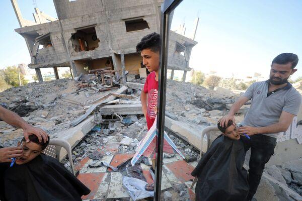 Un  peluquero atiende a un cliente sobre las ruinas de su peluquería. - Sputnik Mundo