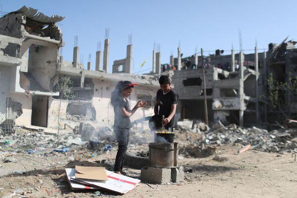 Según  los datos de la Oficina de Coordinación de Asuntos Humanitarios de la ONU, durante el conflicto palestino-israelí de 11 días en la Franja de Gaza fueron dañados o destruidos casi 17.000 edificios, incluidos los residenciales, por lo cual más de 80.000 personas  fueron privadas de condiciones de vivienda normales.En la foto: los niños palestinos preparan maíz caliente al lado de las ruinas de su casa en la Franja de Gaza. - Sputnik Mundo