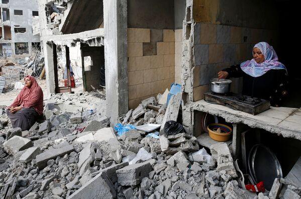 Una  mujer prepara comida en la cocina en su casa destruida. - Sputnik Mundo