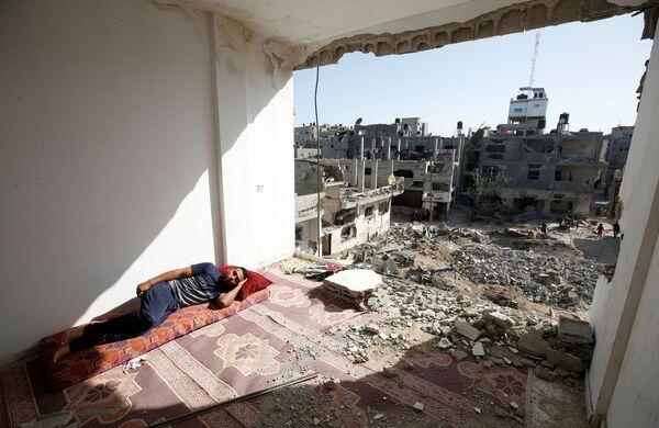 La  ONU informa que alrededor de 800.000 personas en la Franja de Gaza no tienen acceso permanente al agua potable, ya que casi un 50% del sistema de abastecimiento de aguas fue dañado por los ataques aéreos israelíes. En la foto: un palestino duerme en su hogar  destruido. - Sputnik Mundo