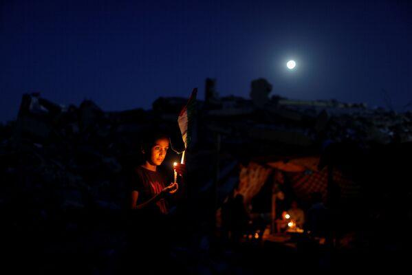 Un  palestino con una vela sobre las ruinas de su casa. - Sputnik Mundo