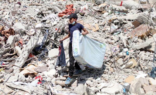 Según  el director regional del Comité Internacional de la Cruz Roja, Fabrizio Carboni, los palestinos tardarán años en reconstruir las casas que fueron destruidas y mucho más tiempo para normalizar sus vidas. En la foto: un niño palestino sobre las ruinas de una  casa destruida.  - Sputnik Mundo