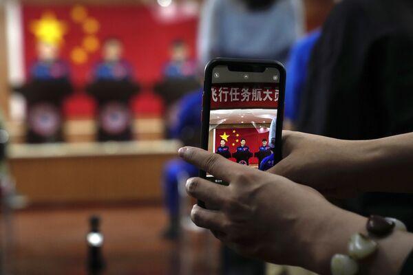 Un periodista fotografía a los taikonautas chinos durante una rueda de prensa en Jiuquan. - Sputnik Mundo
