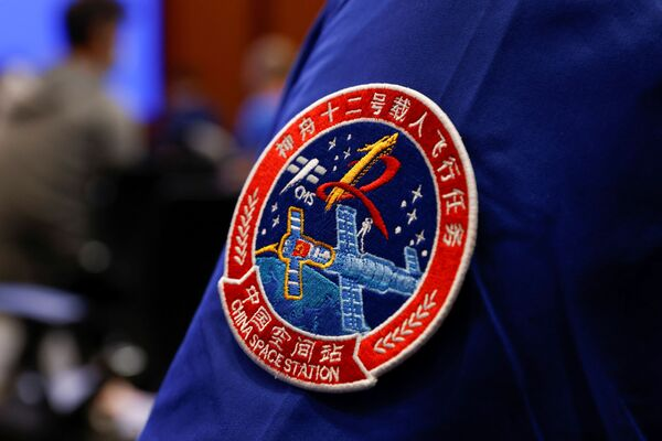 La tripulación actual permanecerá en órbita hasta septiembre, tras lo cual será sustituida por otros tres taikonautas. En la foto, el emblema de la misión espacial tripulada Shenzhou 12. - Sputnik Mundo