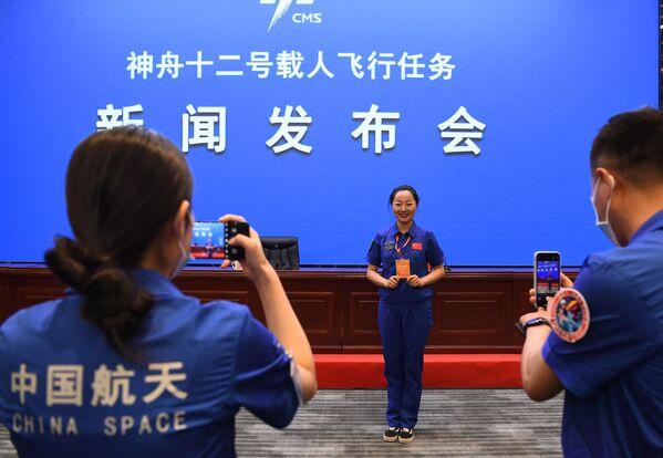 Los empleados del Jiuquan Satellite Launch Center se hacen fotos antes de la rueda de prensa. - Sputnik Mundo