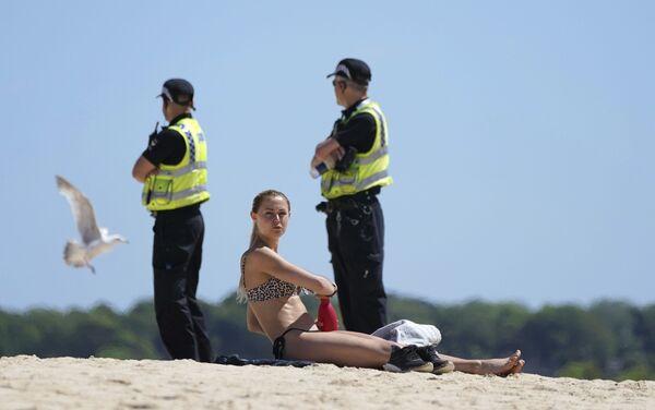 Una mujer se broncea, mientras una patrulla de policía vigila la playa de St. Ives, Cornualles, Reino Unido, durante la reunión de los líderes del G7.  - Sputnik Mundo