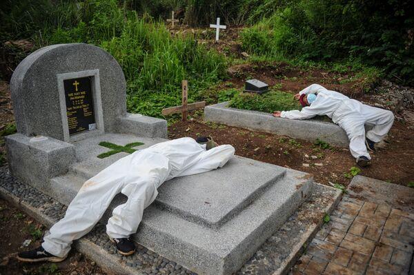Dos hombres que trabajan sepultando personas en un cementerio descansan tras los masivos entierros por el COVID-19 en Bandung, Indonesia. - Sputnik Mundo