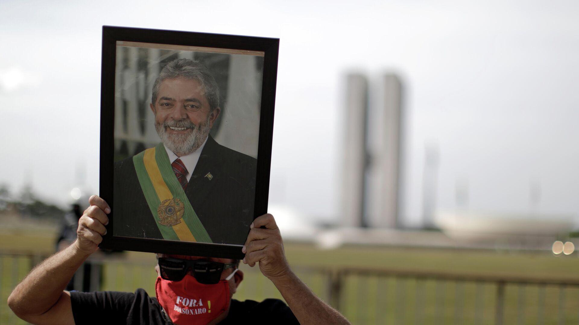 Un manofestante con el retrato del expresidente de Brasil Luiz Inácio Lula da Silva - Sputnik Mundo, 1920, 21.06.2021