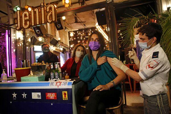 Israel es el líder mundial en la campaña de vacunación. En este país quienes se vacunaron recibieron alimentos y zumos. En la foto: la vacunación en un bar de Tel Aviv, donde los vacunados recibieron una bebida gratuita como premio. - Sputnik Mundo