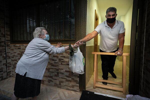 Una mujer de 85 años acude a un reparto de comida en Valencia - Sputnik Mundo