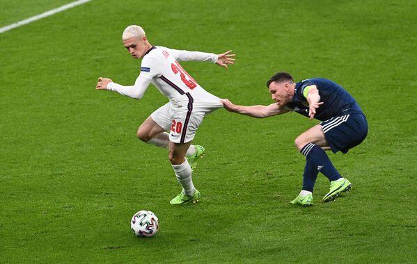 Phil Foden (el Reino Unido) y Andrew Robertson (Escocia) luchan por el balón en el partido de la fase de grupos de la Eurocopa 2020 en el estadio de Wembley, en Londres. - Sputnik Mundo