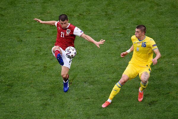 Stefan Lainer (Austria) y Vitaliy Mykolenko (Ucrania) durante un partido de la fase grupal en Bucarest. - Sputnik Mundo