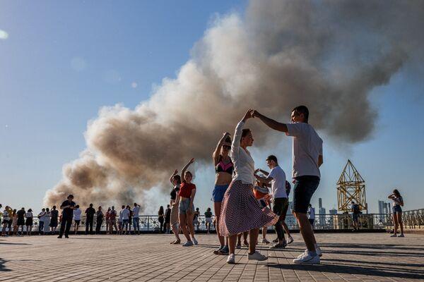 Unas parejas bailan samba con el humo de un almacén pirotécnico en llamas en Moscú de fondo. - Sputnik Mundo