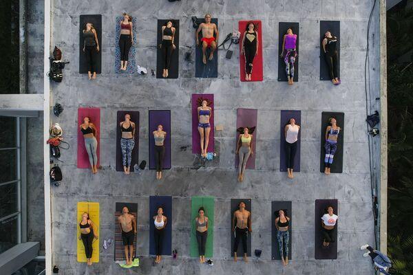 Personas practican yoga en el techo del estudio ARA Yoga Caracas, en Venezuela. - Sputnik Mundo
