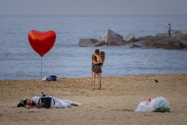 Unos enamorados a primera hora de la mañana en la playa de Barcelona, España. - Sputnik Mundo