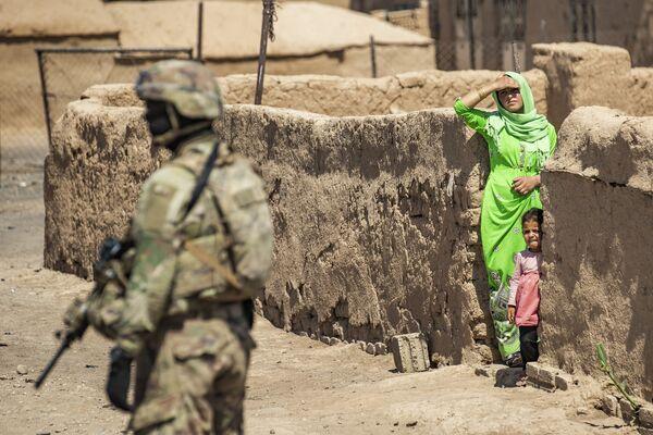 Un soldado estadounidense patrulla una calle de Rumaylan, en el noreste de Siria, junto a unos residentes locales. - Sputnik Mundo