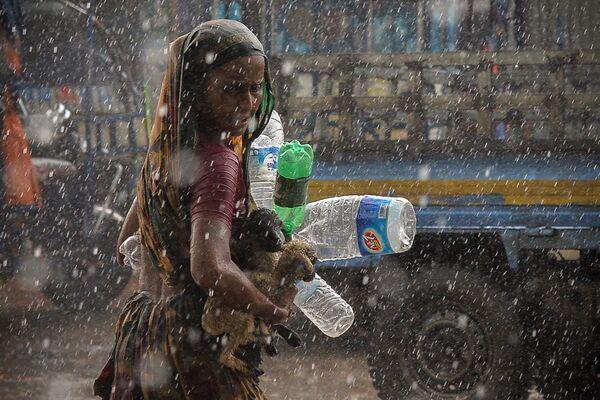 Una mujer bajo la lluvia torrencial en la ciudad de Daca, Bangladés. - Sputnik Mundo
