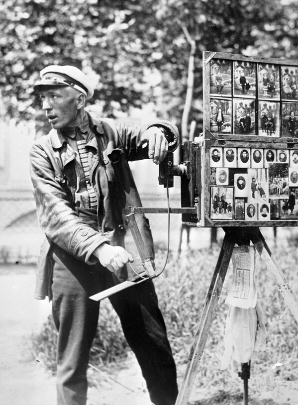 Uno de los prototipos de la película fotográfica moderna contaba con 12 hojas de papel fotosensible y pesaba 15 kilogramos.En la foto: un fotógrafo callejero en 1922.  - Sputnik Mundo