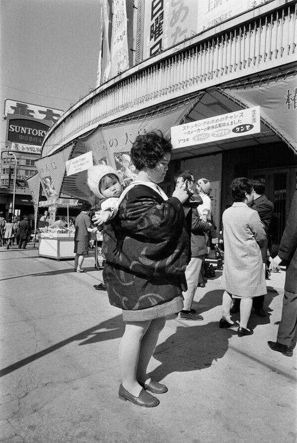 Hoy la mayoría de los teléfonos incorporan una cámara, lo que le permite a las personas registrar cada momento de sus vidas.En la foto: una mujer japonesa con un niño y una cámara en una calle de Tokio en 1972. - Sputnik Mundo