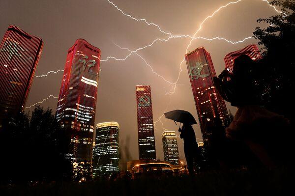 Un rayo atraviesa el cielo durante un espectáculo de luces en Pekín. - Sputnik Mundo
