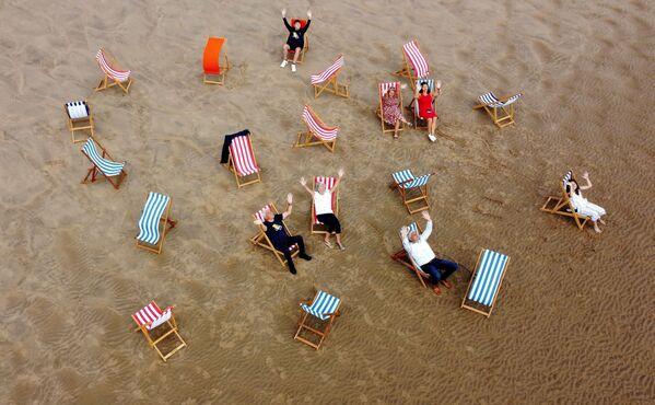 La gente se hace fotos en las tumbonas de la playa británica de Blackpool. Se vuelven a alquilar tras un paréntesis de 10 años. - Sputnik Mundo