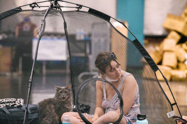 Una mujer y su gato se cobijan de la ola de calor en el Centro de Convenciones de Portland, en Estados Unidos. - Sputnik Mundo