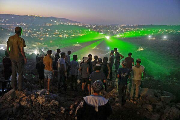 Colonos judíos del puesto de avanzada Eviatar, construido en las afueras de la aldea árabe de Beita, en Cisjordania, observan cómo los palestinos les apuntan con punteros láser para protestar contra la expansión de los asentamientos judíos. - Sputnik Mundo