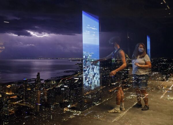 El reflejo de varias personas en los cristales de la Torre Willis de Chicago (EEUU) con truenos de fondo sobre el lago Michigan. - Sputnik Mundo