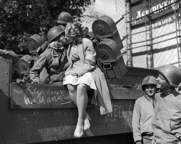 Una mujer de la ciudad belga Lieja, recién liberada de los nazis, besa a un soldado estadounidense, 1944. - Sputnik Mundo