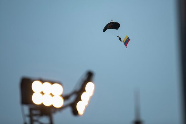 Un paracaidista con bandera venezolana aterriza en pleno desfile. - Sputnik Mundo