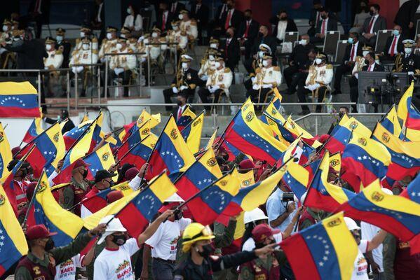 La sangrienta guerra por la independencia duró diez años y terminó en 1821. En la foto: miembros de la Guardia Nacional Bolivariana alzan banderas nacionales durante el desfile. - Sputnik Mundo