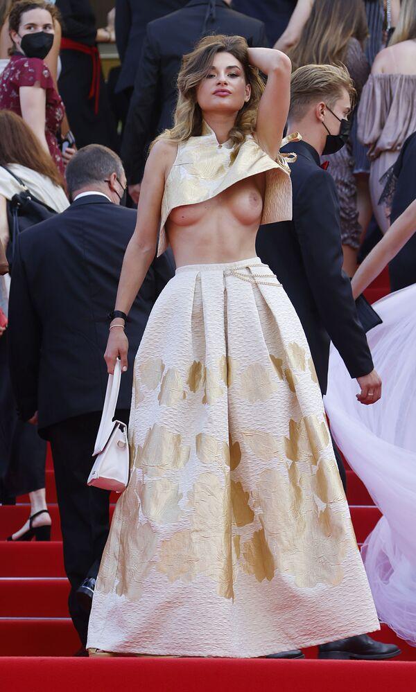 Una invitada del festival de cine asiste al evento con un osado atuendo que deja a la vista uno de sus senos. - Sputnik Mundo