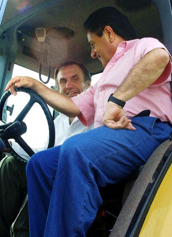 Carlos Reutemann en un tractor junto al expresidente argentino Eduardo Duhalde (2002-2003), conversando sobre una posible candidatura presidencial del expiloto de Fórmula 1 por el Partido Justicialista argentino, para las elecciones del 19 de enero de 2003. Estancia Los Guasunchos, provincia de Santa Fe. 11 julio de 2002.  - Sputnik Mundo