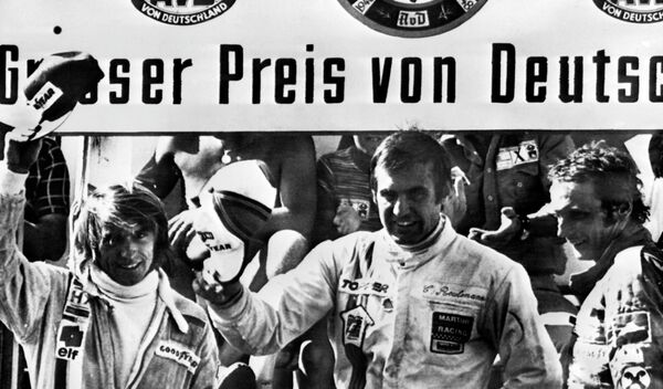Carlos Reutemann saluda desde el podio tras consagrarse ganador del Gran Premio de Alemania de Fórmula 1, junto al francés Jacques Laffite (2º) y al austriaco Niki Lauda (3º). Nürburgring, 3 de agosto de 1975. - Sputnik Mundo