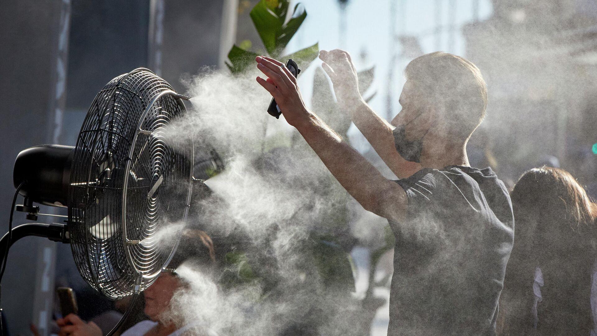 Un chico se refresca del calor con un difusor de vapor de agua de un restaurante de la calle Alcalá en Madrid - Sputnik Mundo, 1920, 10.08.2021