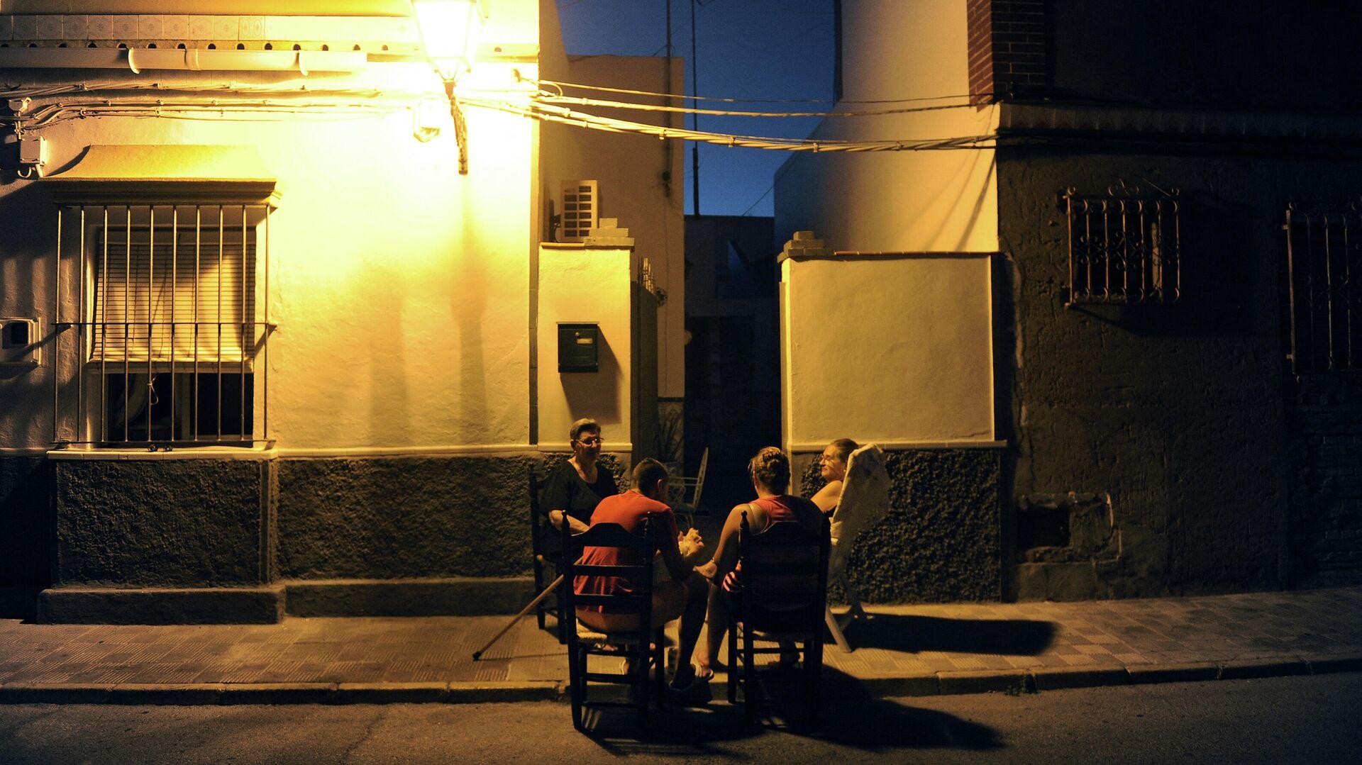 Personas sentadas fuera de su domicilio en  Bollullos de la Mitaciуn (Sevilla) - Sputnik Mundo, 1920, 08.07.2021