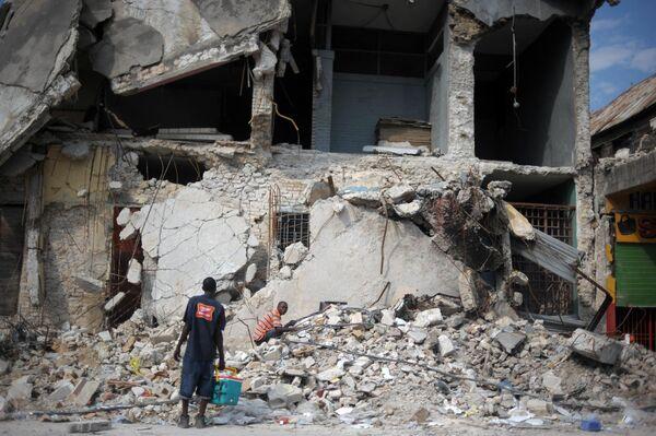 Haitianos buscan entre los escombros de un edificio derruido por el terremoto de magnitud 7,0 en la escala de Richter que se registró el 12 de enero de 2010, con epicentro a 15 kilómetros de la capital, Puerto Príncipe.  Murieron más de 316.000 personas, hubo más de 350.000 heridos y cerca de 1,5 millones de personas quedaron sin hogar. - Sputnik Mundo